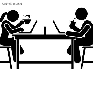 Two people sitting at laptops working.